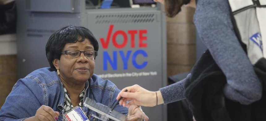 A polling site inspector checks in a voter during early voting last year in New York City. New York, along with a handful of other states, is expanding ballot access.