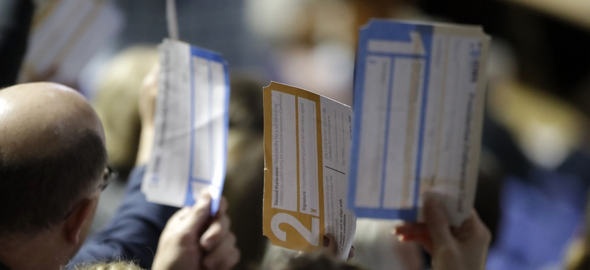 Iowa caucus voters hold up their first votes on Feb. 3, 2020.