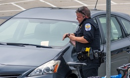 Parking enforcement writes a ticket in San Francisco. The city recently reevaluated its parking ticket fines and fees.