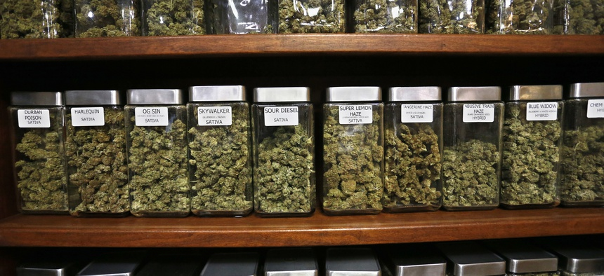 "Glass containers display varieties of marijuana for sale on shelves at The Station, a retail and medical cannabis dispensary, in Boulder, Colorado. Gov. Jared Polis said his state is ""years ahead"" of other states in terms of marijuana legislation."