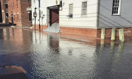 High tide floods a street Friday, Nov. 18, 2016, in Portland, Maine