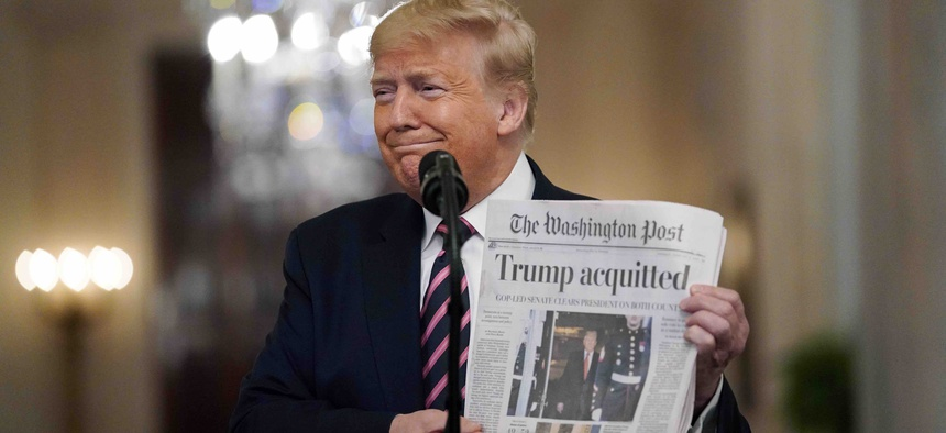 "President Donald Trump holds a copy of The Washington Post as he speaks in the East Room of the White House, Thursday, Feb. 6, 2020, in Washington. Trump has described the news outlet and others as ""fake news"" during the course of his presidency."
