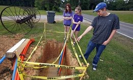 In this May 8, 2019, photograph, Riley Shaw, right, and his youngest sister, Leah, center, and his twin, Abigail, stand around a fiber-optic line that is expected to bring the Shaw family internet service to their home outside Starkville, Miss.