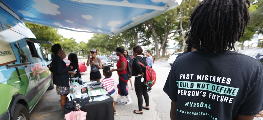 In this 2018 photo, people gather to learn about learn about Florida's Amendment 4, which asked voters to restore the voting rights of people with past felony convictions. Voters approved the amendment in November that year.