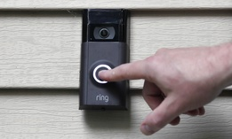 In this Tuesday, July 16, 2019, file photo, Ernie Field pushes the doorbell on his Ring doorbell camera at his home in Wolcott, Conn.