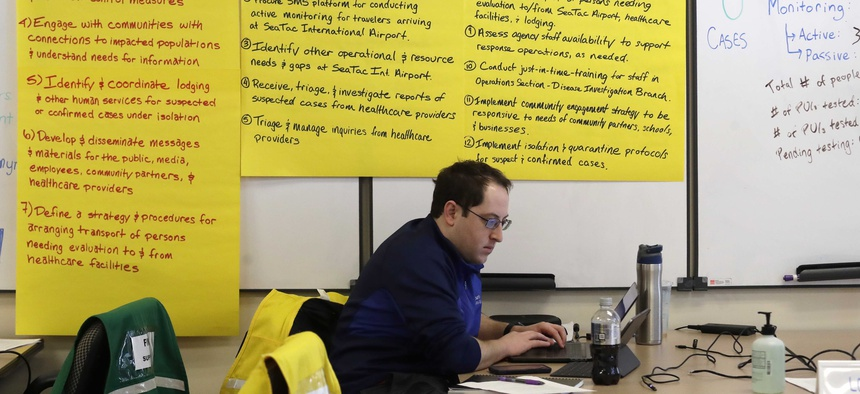In this photo taken Thursday, Feb. 13, 2020, Ted Toet, of the King County Emergency Management office, helps with logistics at the offices of Seattle & King County  Public Health in response to the threat of coronavirus.