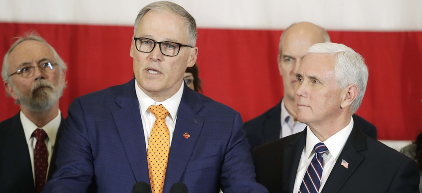 Vice President Mike Pence, right, looks on as Gov. Jay Inslee speaks during a news conference, Thursday, March 5, 2020, at Camp Murray in Washington state. Pence was in Washington to discuss the state's efforts to fight the COVID-19 coronavirus.