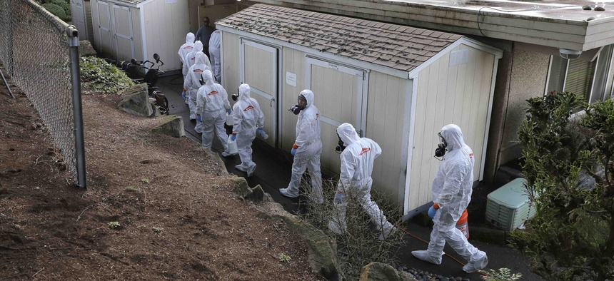 Workers from a Servpro disaster recovery team wearing protective suits and respirators enter the Life Care Center in Kirkland, Wash., to begin cleaning and disinfecting the facility, Wednesday, March 11, 2020, near Seattle.