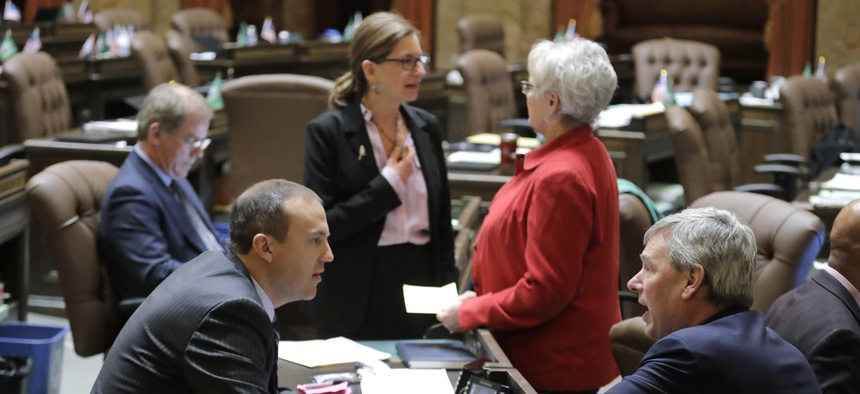 Washington state Rep. Pat Sullivan, lower right, talks with state Rep. Marcus Riccelli, lower left, both Democrats, on the House floor last month. Washington state is scrambling to address the coronavirus outbreak as its legislative session winds down.