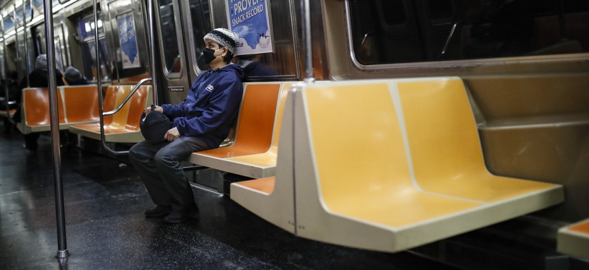 A commuter wears a face mask while riding the a nearly empty subway car into Brooklyn, Thursday, March 12, 2020, in New York.
