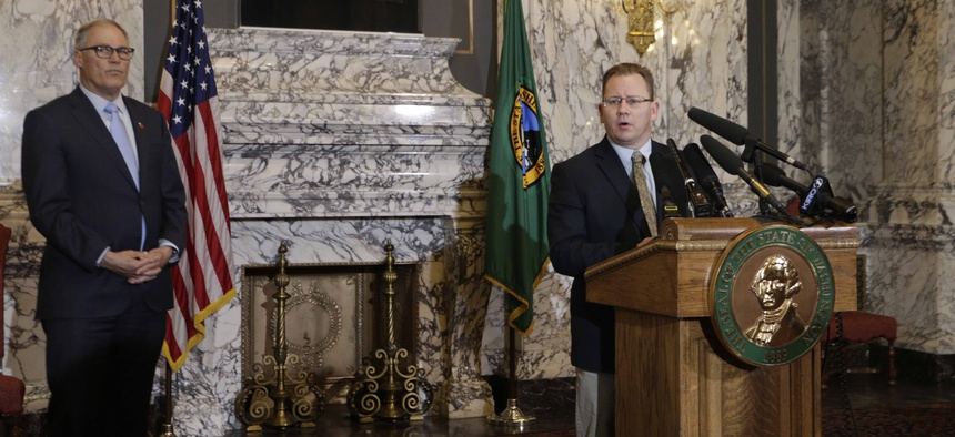 State Superintendent of Public Instruction Chris Reykdal, right, talks to the media about the decision to close all schools in the state in response to COVID-19, as Gov. Jay Inslee looks on, Friday, March 13, 2020, in Olympia, Wash.