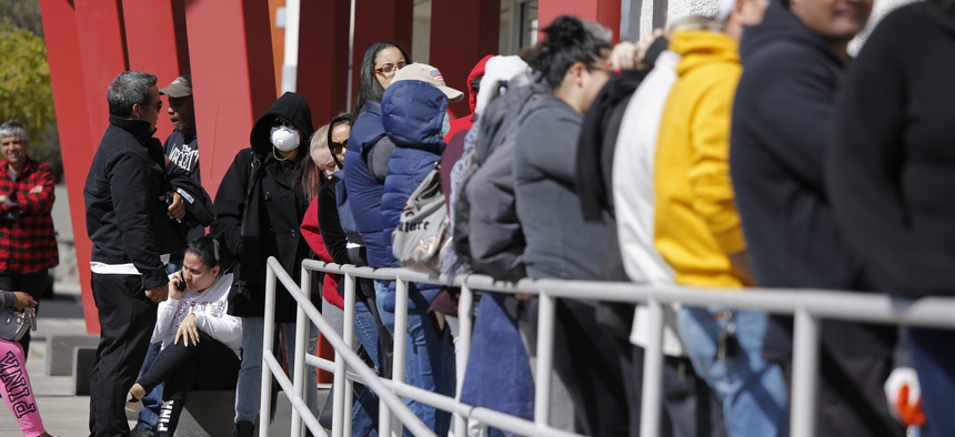 People wait in line for help with unemployment benefits at the One-Stop Career Center, Tuesday, March 17, 2020, in Las Vegas.