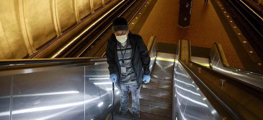 Andre of Washington, D.C., rides the escalator up at the Metro subway Congress Heights train station in Washington, Friday, March, 13, 2020. He wears two face masks and gloves to protect his children and grandchildren from the coronavirus.