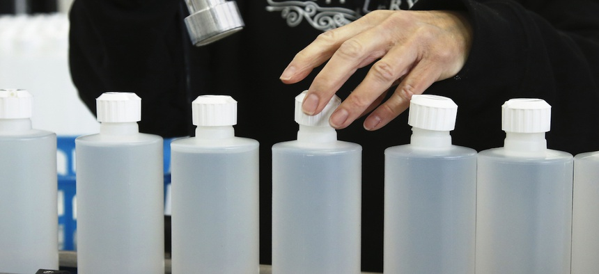 Rhonda Gillett caps bottles of hand sanitizer at the Prairie Distillery, which has switched from making liquor to making hand sanitizer due to the coronavirus pandemic, in Guthrie, Okla., Saturday, March 21, 2020.