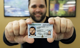 Ryan Norris, a license service representative at the Washington state Dept. of Licensing office in Lacey, Wash., poses for a photo Friday, June 22, 2018 while holding a sample copy of a Washington drivers license.