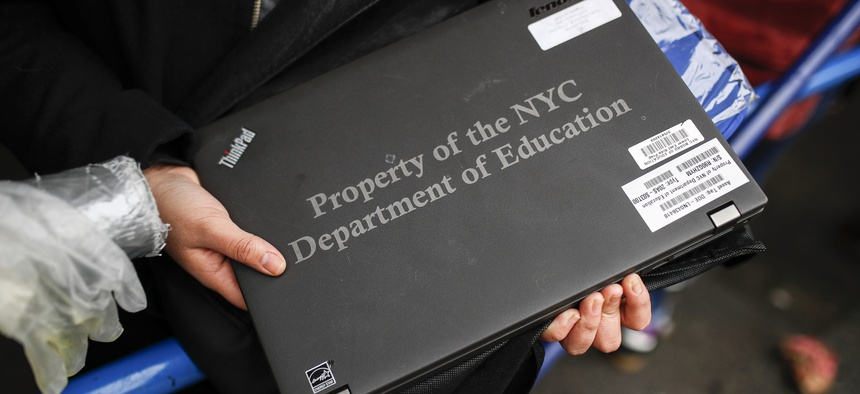 A student receives her school laptop for home study at the Lower East Side Preparatory School in New York.