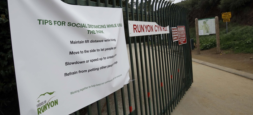 A signs issues instructions for social distancing as Runyon Canyon park announces a closure Wednesday, March 25, 2020, in Los Angeles.