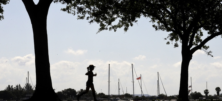 A runner makes her way along the Davis Islands Yacht Basin on a beautiful spring day, Wednesday, March 25, 2020, in Tampa, Fla.