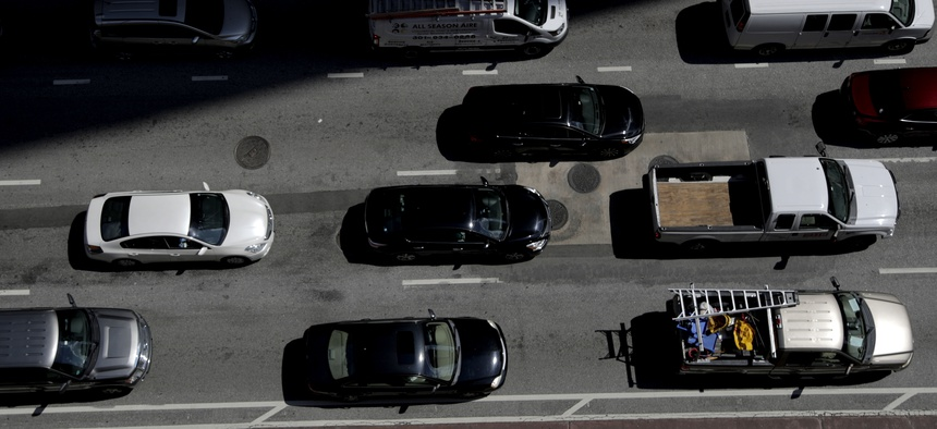 In this July 2, 2019, file photo vehicles wait for a green light in downtown Baltimore.