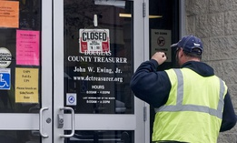 A man is confronted with a closed sign at the Douglas County Treasurer's office in Omaha, Neb. on March 18, 2020. In-person services were suspended due to the coronavirus outbreak.