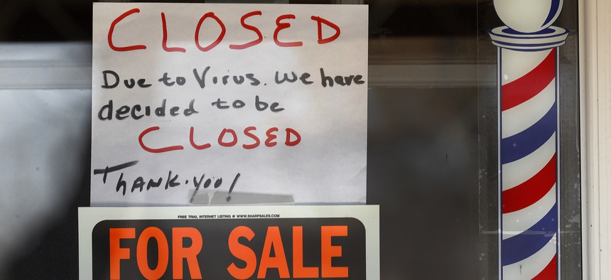 """For Sale By Owner"" and ""Closed Due to Virus"" signs are displayed in the window of Images On Mack in Grosse Pointe Woods, Mich., Thursday, April 2, 2020."