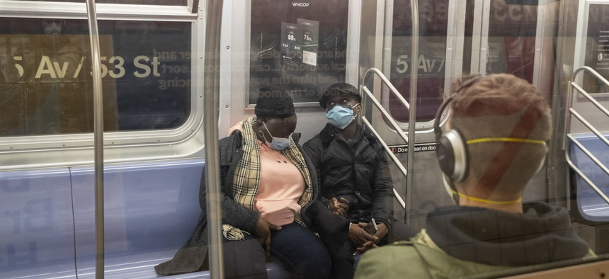 Riders on the New York City subway wear face masks. African Americans are more likely to live in dense urban areas that rely on public transportation.