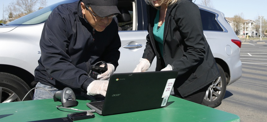 Wilbert Villalta, left, and Lindsey Lilley, right, employees of the Elk Grove Unified School District, register a Chromebook to be assigned to a student in the district, at Monterey Trail High School in Elk Grove, Calif., Thursday, April 2, 2020.