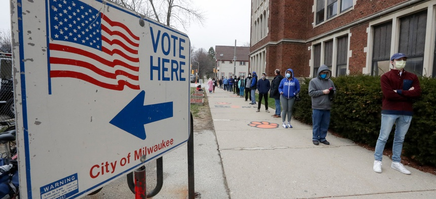 Voters line up at Riverside High School for Wisconsin's primary election Tuesday April 7, 2020, in Milwaukee.