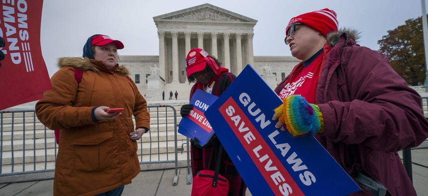 Activists gather outside the Supreme Court before the justices hear arguments in a case brought by gun owners in New York City, on Capitol Hill in Washington, Monday, Dec. 2, 2019.