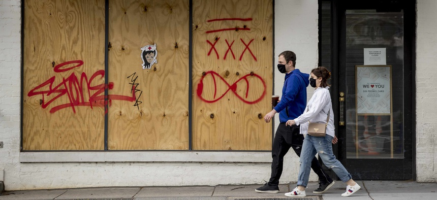 People in masks to protect against coronavirus, walk past a boarded up storefront along 14th Street in Northwest Washington, Wednesday, April 29, 2020.