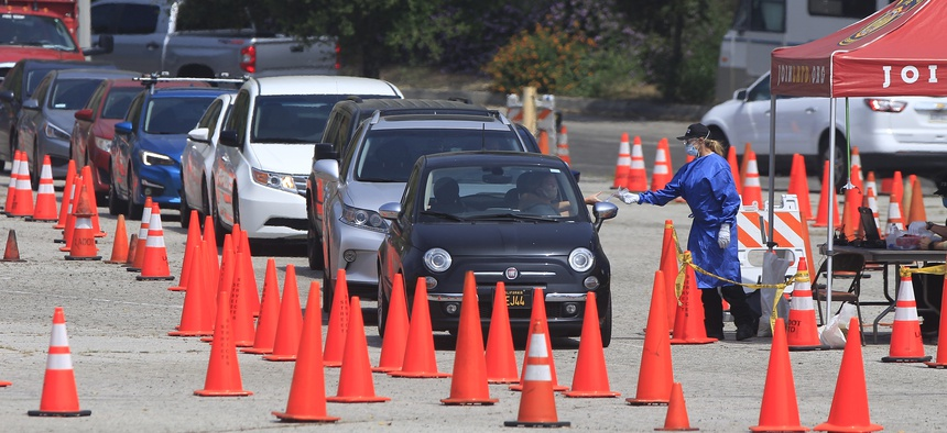 Los Angeles Fire Department officials wearing protective gear deliver testing kits to a waiting motorists at a COVID-19 drive-thru testing site in Elysian Park, Los Angeles on April 30, 2020.