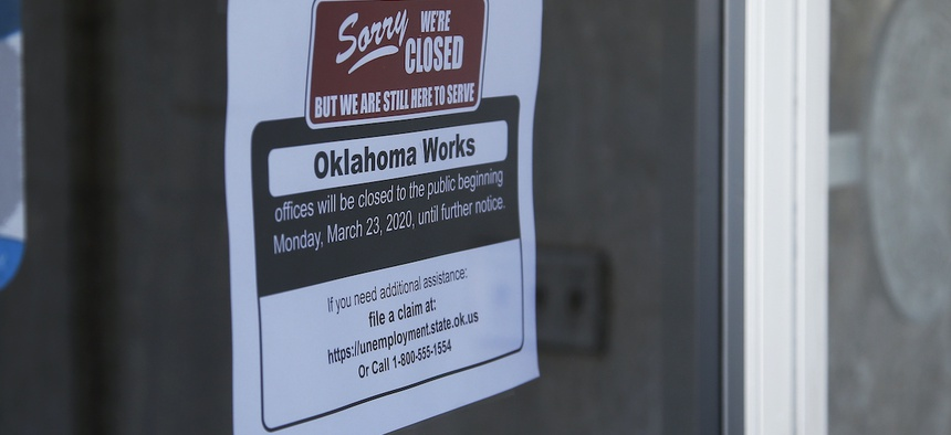 A sign at the Oklahoma Employment Security Commission offices states the offices are closed, Thursday, April 23, 2020, due to the coronavirus, in Oklahoma City.