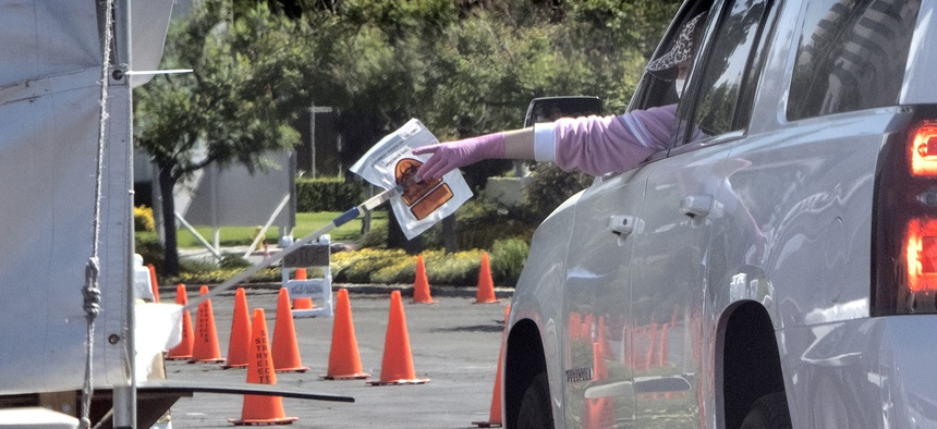 In this Wednesday, May 6, 2020 photo a medical worker passes a self administered coronavirus test on a pole to a passenger in a car at a drive-thru testing site in the Woodland Hills section of Los Angeles.