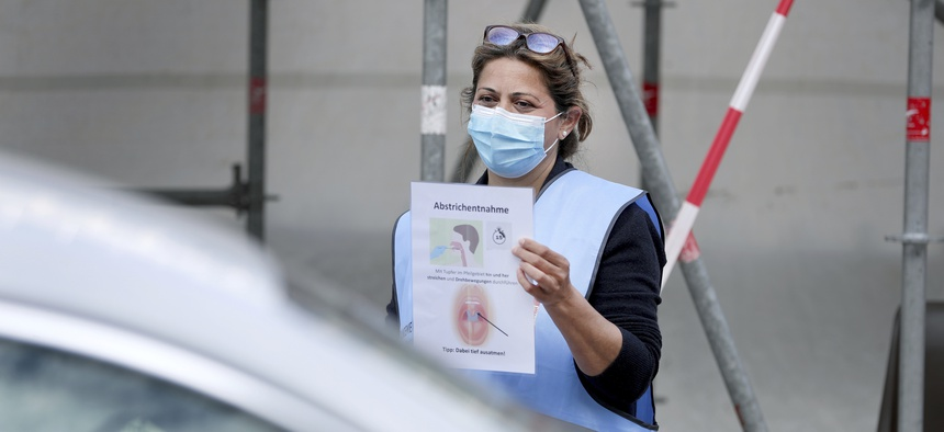 A staff member of the local health authority holds an information poster on how to use a new coronavirus test kit at a new drive-in testing center in Berlin, Germany on April 24, 2020.