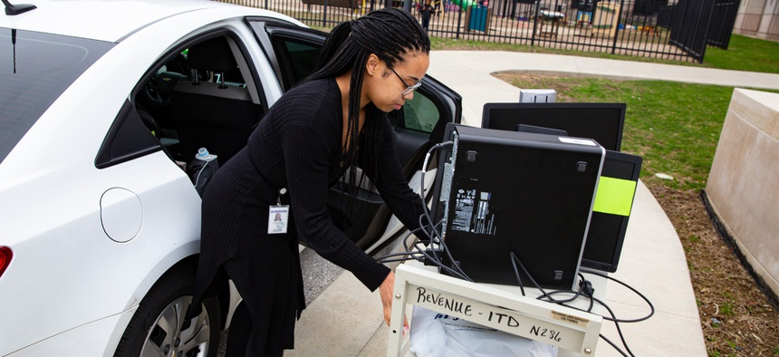 An employee at the Indiana Department of Revenue moves her computer equipment from her office at the State office complex in Indianapolis on March 24, 2020, to allow her to work from home.