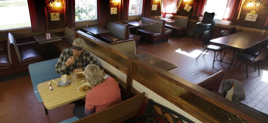 Customers Randy and Nancy Cree eat dinner in the dining room of the Chic-A-Dee Cafe In Topeka, Kan., Tuesday, May 5, 2020. Some booths are closed in order to maintain distance.