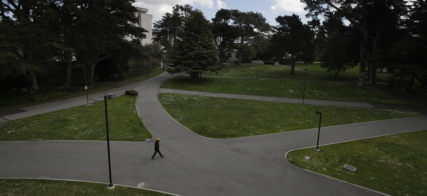 A man walks alone on a path on the campus of San Francisco State University, part of the California State University system, on March 19, 2020.