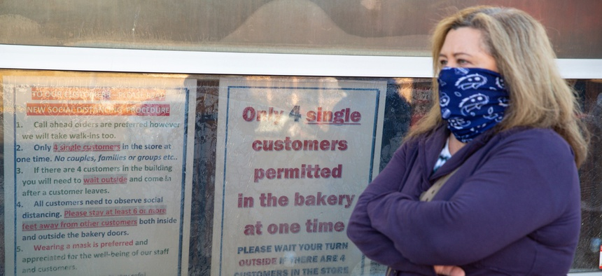 A masked customer waits in line next to a sign outlining the rules to enter at the Long's Bakery Shop in Indianapolis on May 1, 2020 after the bakery reopened after closing it doors due to COVID-19.