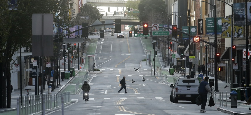 A man crosses a nearly empty street in San Francisco on March 17, 2020.