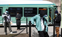 People wait for the bus in Detroit. The city, which has been a coronavirus hotspot, is also one of the top U.S. cities for rates of hypertension, a comorbidity of coronavirus.