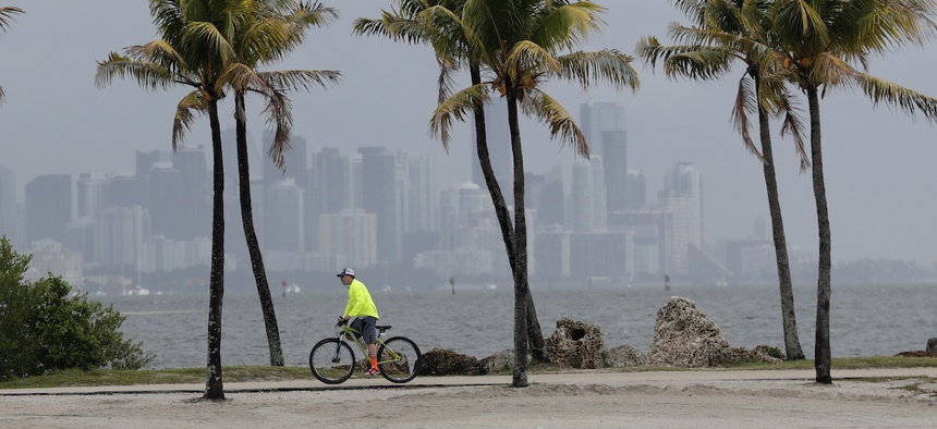 The Miami skyline is shrouded in clouds that would become Tropical Cyclone Arthur as a cyclist rides along Biscayne Bay at Matheson Hammock Park, Friday, May 15, 2020, in Miami.