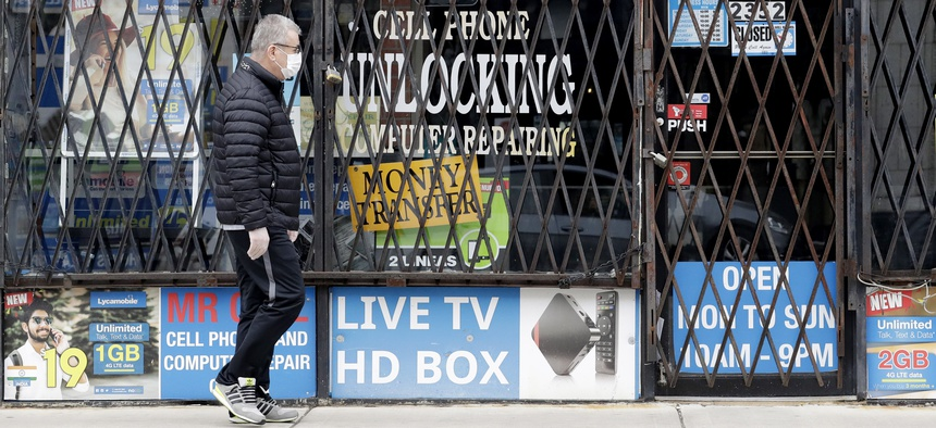 A man walks by a closed store during the COVID-19 in Chicago, Thursday, April 30, 2020.