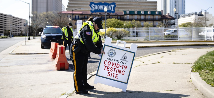An officer sets out a sign ahead of the opening of a COVID-19 test location in a parking lot near the casinos in Atlantic City, N.J. on April 28, 2020.
