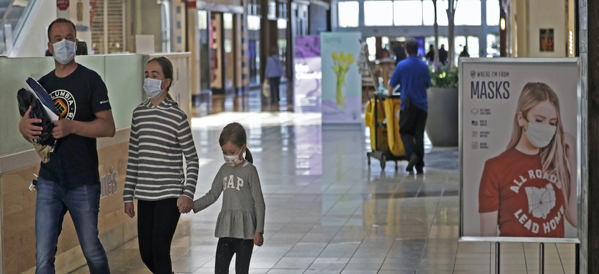 Shoppers walk past a sign encouraging masks at SouthPark Mall, Wednesday, May 13, 2020, in Strongsville, Ohio.