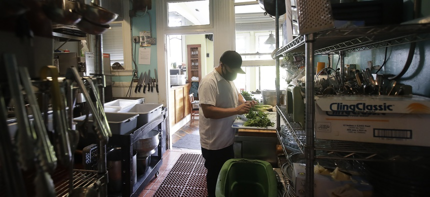 Jesus Cruz, prep cook at Blue Plate, covers his face with a mask while working in the kitchen at the San Francisco restaurant, during the coronavirus outbreak Thursday, May 14, 2020.
