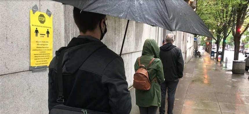 Potential grand jurors wait 6 feet apart to enter the Multnomah County Courthouse in Portland, Oregon, earlier this month. Courts around the country must figure out how to resume operations in a way that keeps employees and visitors safe.