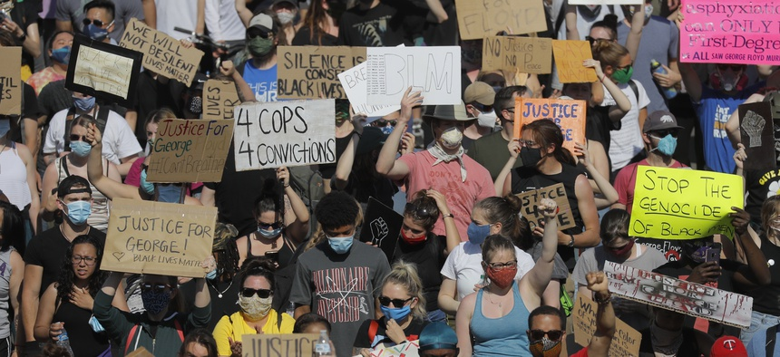 Demonstrators march on pavement, Sunday, May 31, 2020, in Minneapolis. Protests continued following the death of George Floyd, who died after being restrained by Minneapolis police officers on May 25.