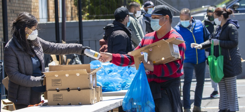 A volunteer distributes groceries at a church food pantry on May 12, 2020, in the Flushing neighborhood of the Queens borough of New York.