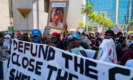 A sign in Miami calls for the police to be defunded.