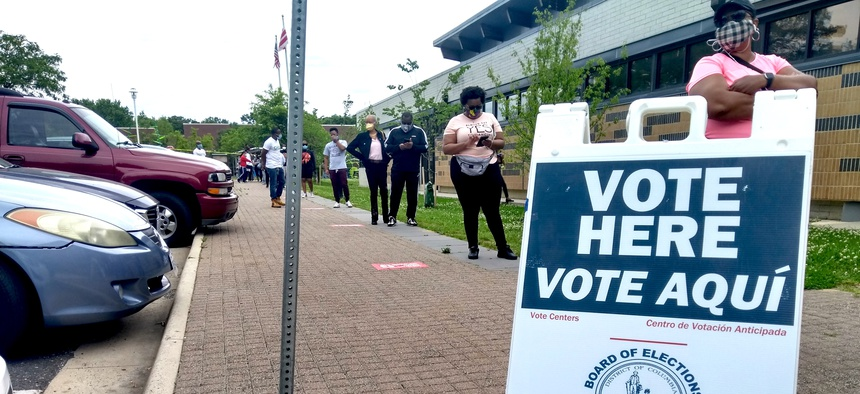 Voters wear masks and maintain distance from one another while they wait in line to cast ballots at the Hillcrest Recreation Center in Washington, D.C. on Tuesday June 2, 2020.